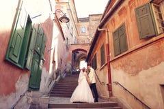 Brud och brudgum som går i gammal stad Royaltyfria Bilder