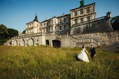 Brud och brudgum som går nära antik slott Fotografering för Bildbyråer