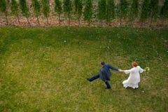 Brud och brudgum som går på det gröna gräset Royaltyfri Bild