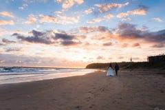 Brud och brudgum som går på en strand i Afrika Arkivfoto