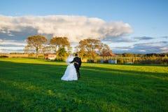 Brud och brudgum som går på fältet Fotografering för Bildbyråer
