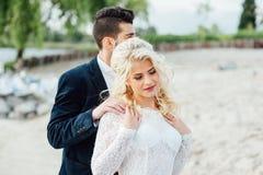Brud och brudgum som går på floden royaltyfria foton
