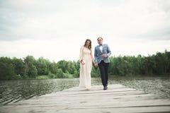 Brud och brudgum som går på floden och att le och att kyssa Arkivfoton