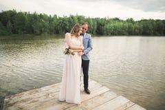Brud och brudgum som går på floden och att le och att kyssa Arkivbild