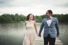 Brud och brudgum som går på floden och att le och att kyssa Royaltyfria Foton
