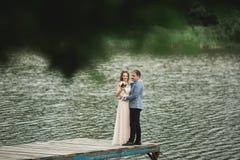 Brud och brudgum som går på floden och att le och att kyssa Arkivbilder