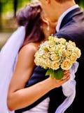 Brud och brudgum som ger den utomhus- blomman Royaltyfri Foto