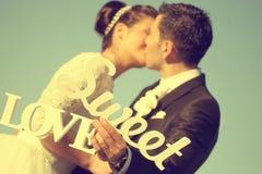 Brud och brudgum som har roligt och poserar med söta förälskelsebokstäver i solljus Royaltyfria Foton