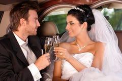 Brud och brudgum som klirrar exponeringsglas Fotografering för Bildbyråer