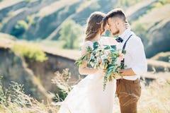 Brud och brudgum som kramar på bröllopet i natur Arkivfoton