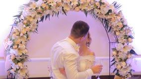 Brud och brudgum som kysser i en restaurang medan lager videofilmer
