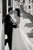 Brud och brudgum som kysser i gatan royaltyfri foto