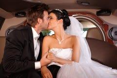 Brud och brudgum som kysser i limo Royaltyfri Foto