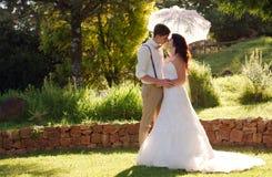 Brud och brudgum som kysser i trädgårds- bröllop Arkivbilder