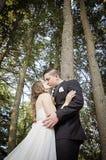 Brud och brudgum som kysser under trees Fotografering för Bildbyråer