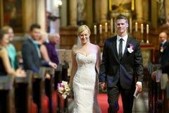 Brud och brudgum som lämnar kyrkan Royaltyfria Bilder