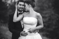 Brud och brudgum som omfamnar sig Fotografering för Bildbyråer