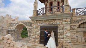 Brud och brudgum som poserar för foto och video nära den storartade slott- och stenväggen stock video