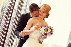 Brud och brudgum som rostar på deras bröllopdag arkivbild