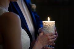 Brud och brudgum som rymmer en stearinljus Arkivfoto