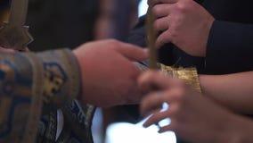 Brud och brudgum som rymmer händer i kyrka på ceremoni stock video
