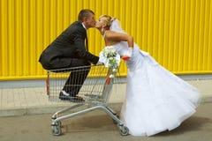 Brud och brudgum som spelar med en korg av supermarket Royaltyfri Foto