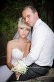 Brud och brudgum som tillsammans poserar utomhus- Fotografering för Bildbyråer