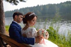 Brud och brudgum som tycker om det härliga landskapsammanträdet på en bänk nära sjön i sommar royaltyfria foton