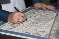 Brud och brudgum som undertecknar ketubahen Fotografering för Bildbyråer
