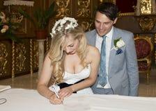 Brud och brudgum som undertecknar registret Arkivfoton