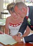 Brud och brudgum som undertecknar registret Arkivbilder