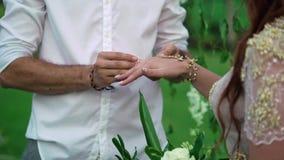 Brud och brudgum som utbyter cirklar på bröllopceremoni arkivfilmer