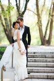 Brud och brudgum som utomhus poserar på bröllopdag Arkivfoto