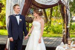 Brud och brudgum under dekorativ bröllopbåge Royaltyfria Foton
