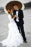 Brud och brudgum under ett paraply Royaltyfri Bild