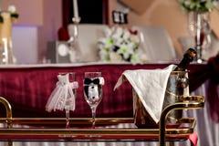 Brud och brudgumexponeringsglas och champagne på den dekorerade tabellen Arkivfoton