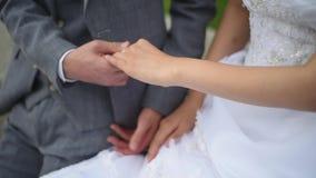 Brud- och brudgumhänder på bröllopdagen lager videofilmer