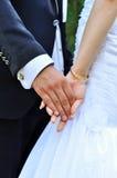 Brud- och brudgumholdinghänder Arkivfoto