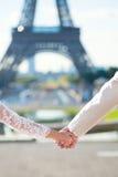 Brud- och brudguminnehavhänder i Paris Royaltyfri Foto