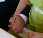 Brud- och brudguminnehavhänder under förbindelseceremoni i borgerligt registreringskontor arkivbilder
