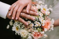 Brud- och brudguminnehavhand på buketten arkivbilder