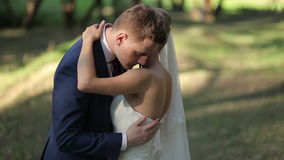 Brud- och brudgumkel som kysser och ler på deras bröllopdag, i parkera stock video