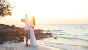 Brud- och brudgumkram mot panelljus på stranden på gryning lager videofilmer