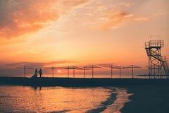 Brud och brudgummen mot en havssolnedgång Arkivbild