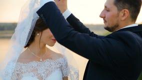 Brud- och brudgumomfamningen på ett bröllop går mot sjön arkivfilmer