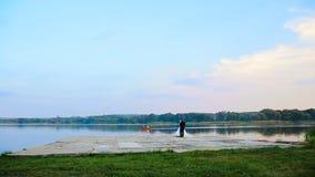 Brud- och brudgumomfamningen på ett bröllop går mot sjön lager videofilmer