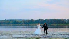 Brud- och brudgumomfamningen på ett bröllop går mot sjön stock video