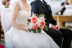 Brud- och brudgumsammanträde under bröllopceremoni Arkivfoto