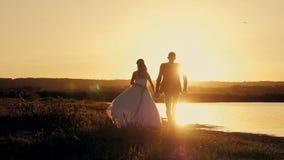 Brud- och brudgumspring till och med fältet som möter solen på solnedgången arkivfilmer