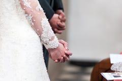 Brud- och brudgumvikninghänder i kyrka royaltyfria bilder